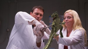 POSEIDON REX (Brian Krause and Anne McDaniels put the pinch on a newly hatched P-Rex) (publicity still)